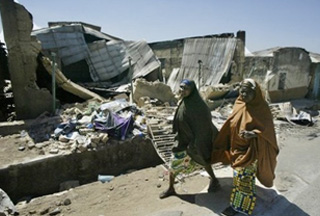Nigerian displaced women walk past a destroyed house {PressTv}